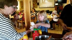 I pausen serverar Kristina korv med bröd.